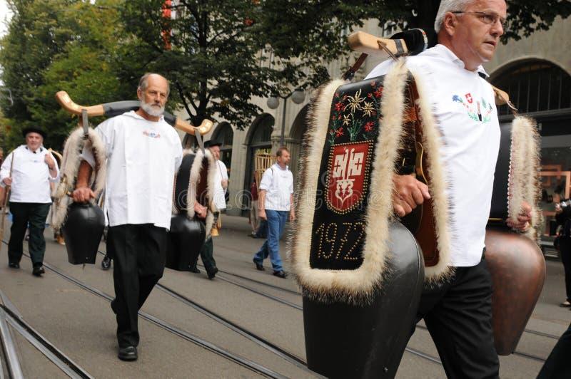 'Treichler 'mit den Kuhglocken, die durch das Bahnhofstreet in ZÃ-¼ Reichen gehen lizenzfreie stockfotos