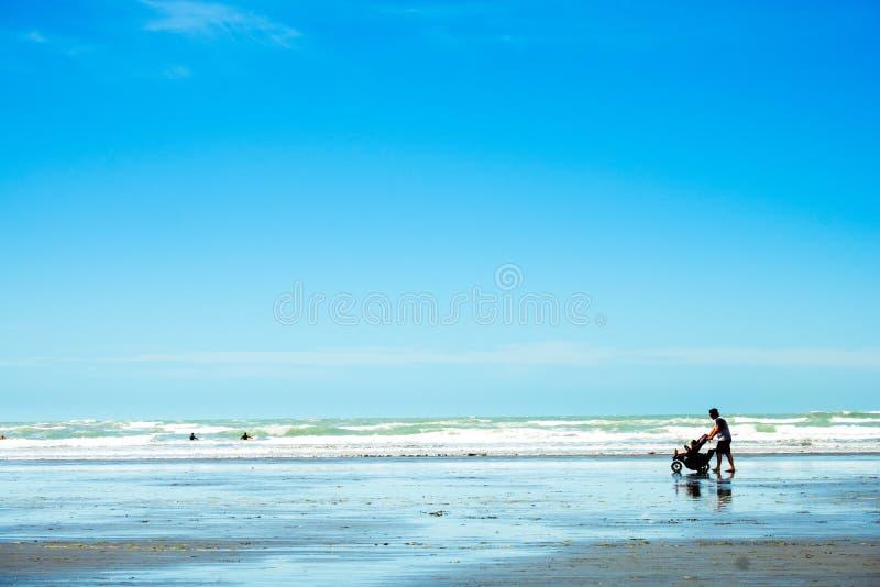 """"""" 2018年,2月4日 — 新西兰克赖斯特彻奇,一位父亲带着婴儿推车中的双胞胎婴儿在阳光灿烂的蓝色沙滩上行走 免版税库存照片"""