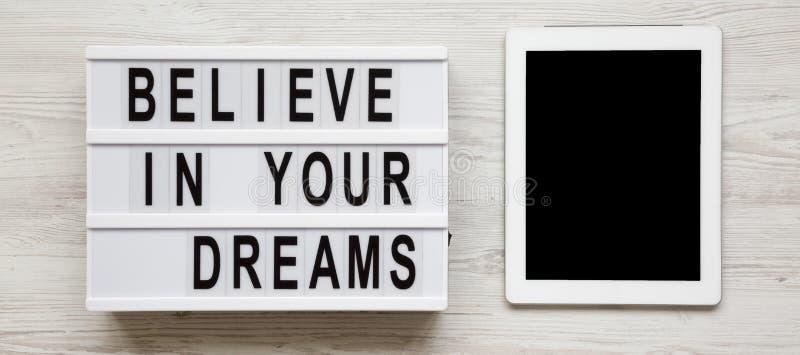 ?Credi nella parola su un lightbox, compressa dei vostri sogni con lo schermo in bianco sopra superficie di legno bianca, vista s fotografia stock libera da diritti