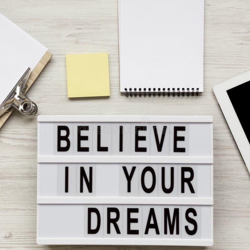 """""""Credi nelle parole dei vostri sogni sul bordo, sulla lavagna per appunti e sulla compressa moderni sopra superficie di legno bia fotografia stock libera da diritti"""