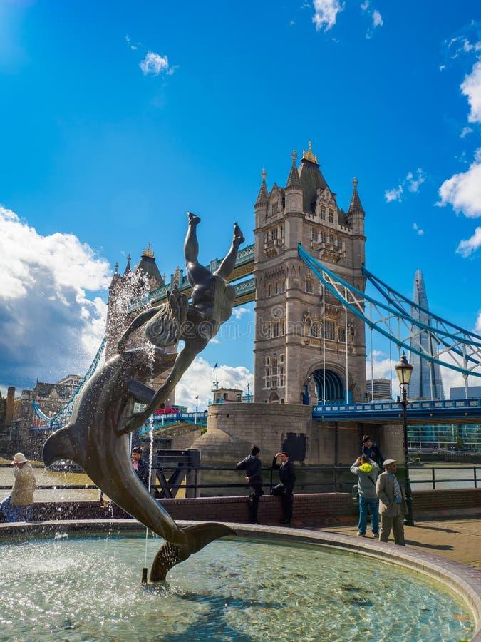 """""""Ragazza con la scultura e la fontana di un delfino """"sul lungomare accanto al ponte della torre a Londra, BRITANNICA un giorno so fotografia stock"""