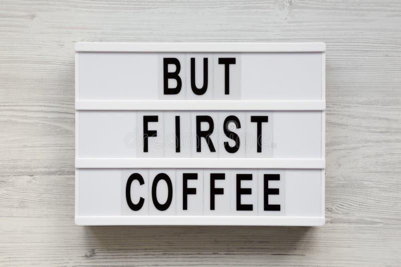 """""""Только слова первого кофе """"на современной доске над белой деревянной предпосылкой, взглядом сверху Надземное, плоское положение, стоковые фото"""