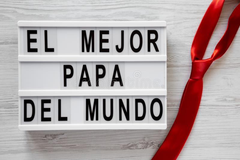 """""""El слова Mejor Папы Del Mundo """"на современной доске, красной связи над белой деревянной предпосылкой, взглядом сверху r стоковое изображение"""