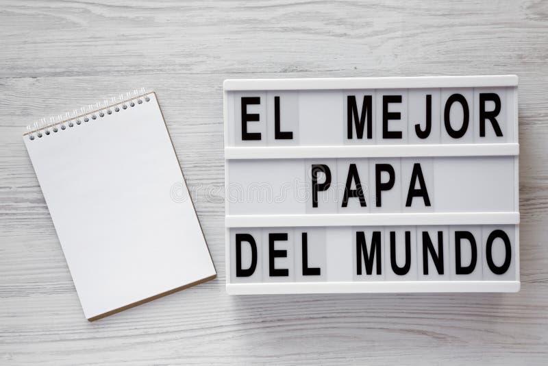 """""""El слова Mejor Папы Del Mundo """"на современной доске, пустом блокноте над белой деревянной предпосылкой, взглядом сверху Наверху, стоковое фото rf"""
