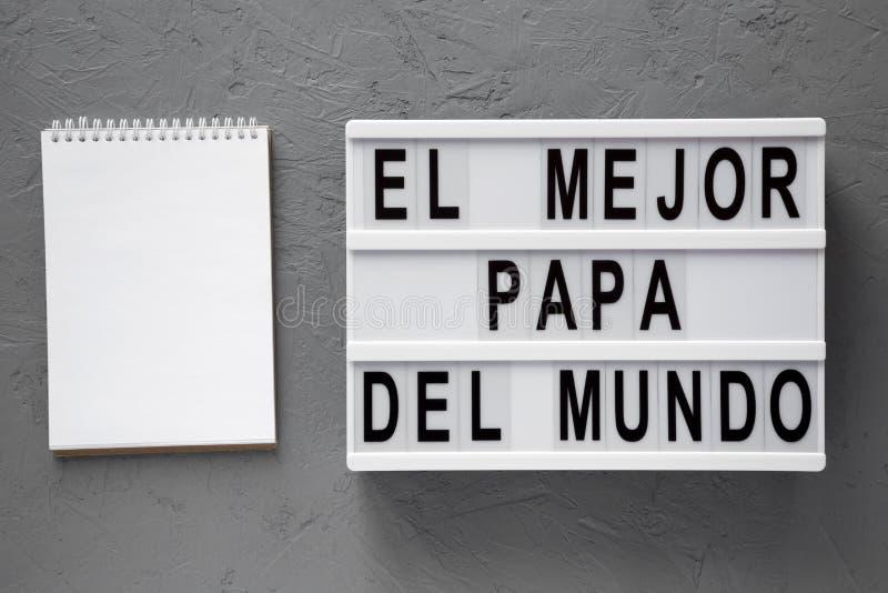 """""""El слова Mejor Папы Del Mundo """"на lightbox, пустом блокноте над серой предпосылкой r День отца стоковая фотография rf"""