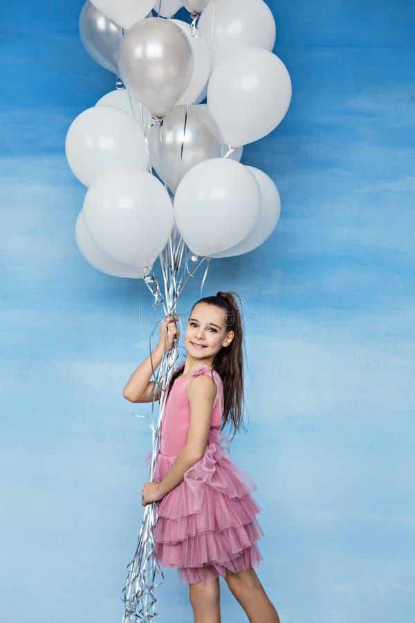有棕色头发的一个美丽的青少年的女孩在拿着很多气球的一件桃红色礼服