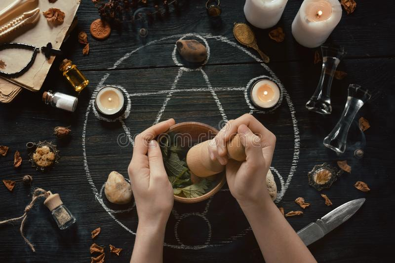 ⁶Womens hands make love potion on pentagram circle with candles, stones and old books on witch table. Occult, esoteric or. The womens hands make love potion on stock photo