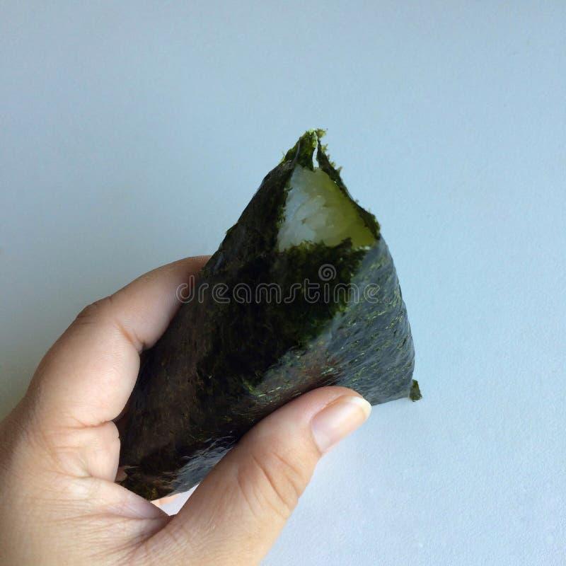 €˜Onikiri' в руке дамы традиционное еды японское стоковое изображение