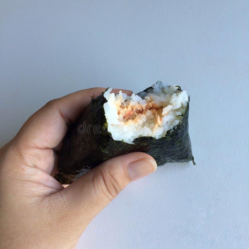 €˜Onikiri' в руке дамы традиционное еды японское стоковые изображения rf