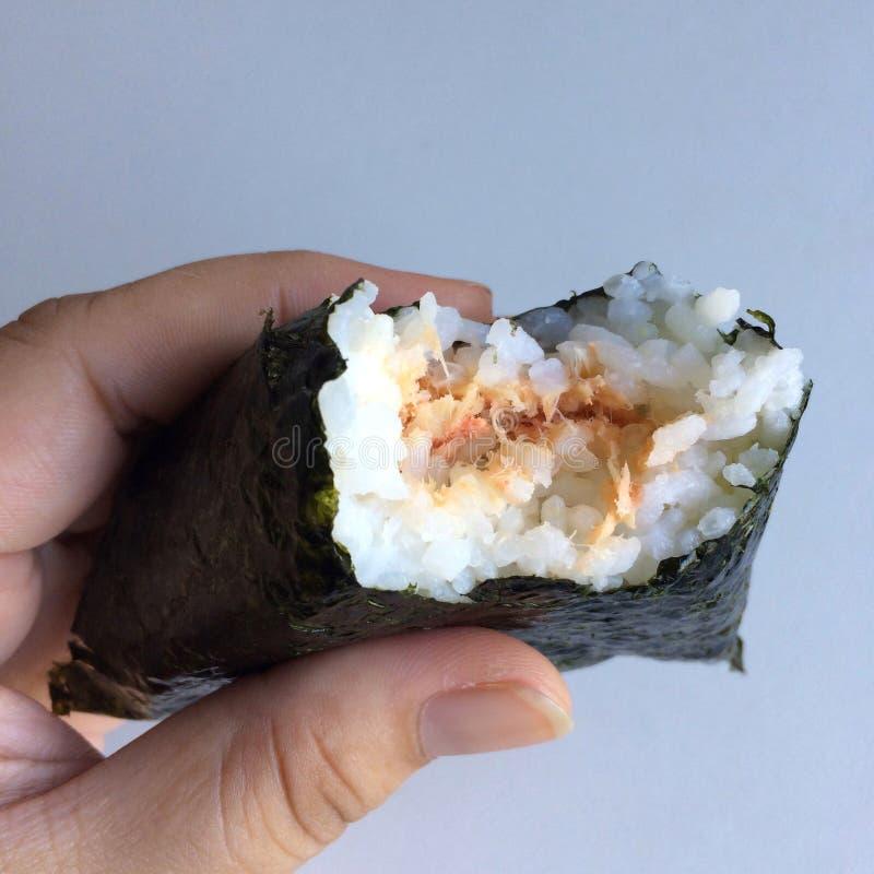 €˜Onikiri' в руке дамы традиционное еды японское стоковое изображение rf