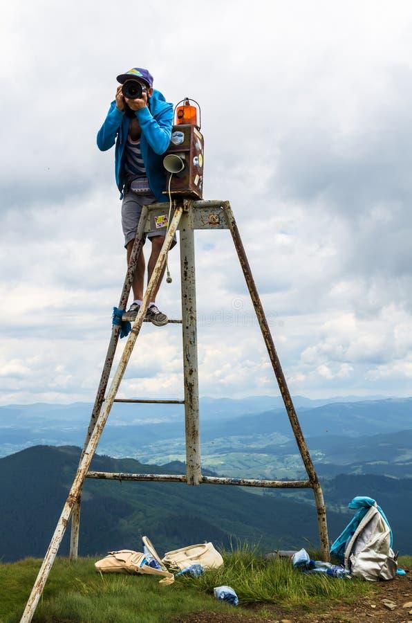 € «июль 2017 УКРАИНЫ: Фотограф na górze горы на работе, прикарпатских горах стоковые фото