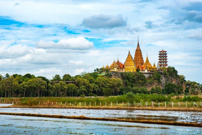 """€ """"Augusti 12, 2018 för KANCHANABURI THAILAND: Tiger Cave Temple i Tha Muang och risfält med träbron royaltyfria foton"""
