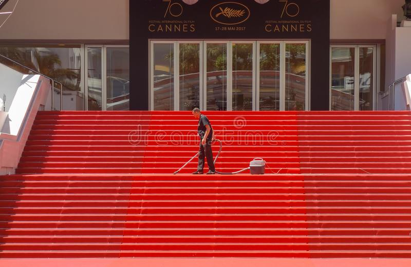 """€ de CANNES, FRANCIA"""" 19 de mayo de 2017: Un hombre limpia los pasos icónicos de la alfombra con la aspiradora roja delante de f imagen de archivo libre de regalías"""