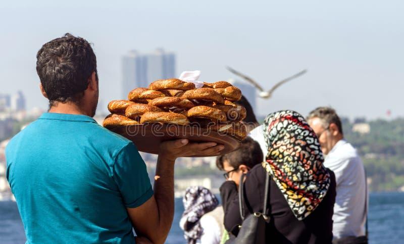 """€ de Estambul, Turquía """"28 de abril de 2018: Un vendedor ambulante lleva los panecillos turcos tradicionales Simit en el terrapl imágenes de archivo libres de regalías"""