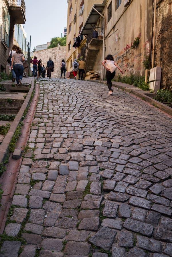 """€ de Istambul, Turquia """"29 de abril de 2018: Os transeuntes andam acima da rua pavimentada estreito em Balat, um dos distritos h imagens de stock"""