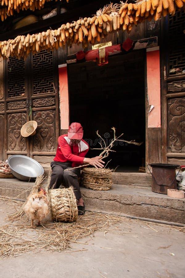 """€ de Yunnan, China """"2 DE MARZO DE 2012: Viejo hombre chino que hace una silla del maíz delante de la casa china encantadora viej imágenes de archivo libres de regalías"""