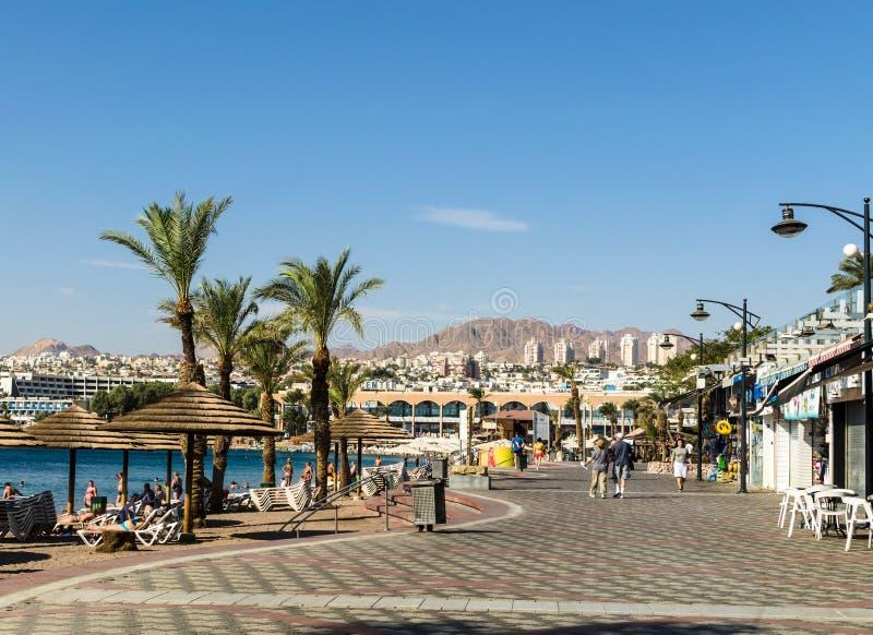 """€ ELATS, ISRAEL """"am 7. November 2017: Stadtpromenade, gehende Touristen, Palmen und Strand mit sunbeds und Regenschirmen, Elat,  stockfotografie"""