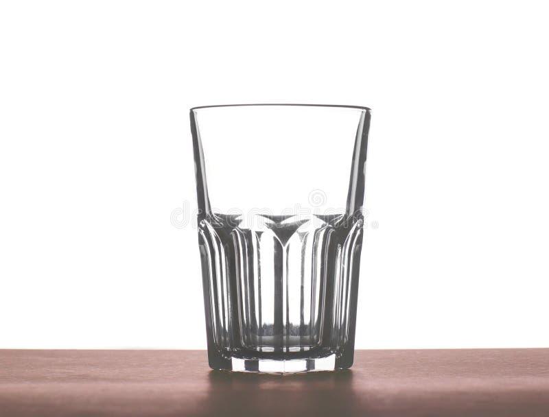 水、汁液或者牛奶的一块大美丽的空的玻璃在一张黑褐色木桌上,隔绝在白色背景 免版税库存图片