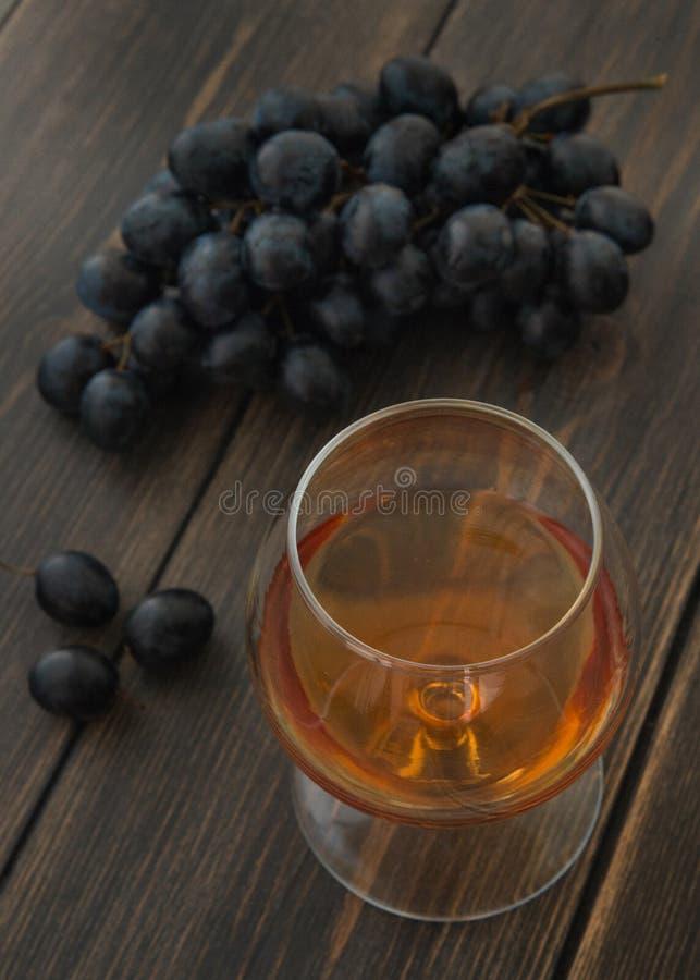 一一口威士忌酒科涅克白兰地或白兰地酒与一束葡萄 免版税图库摄影
