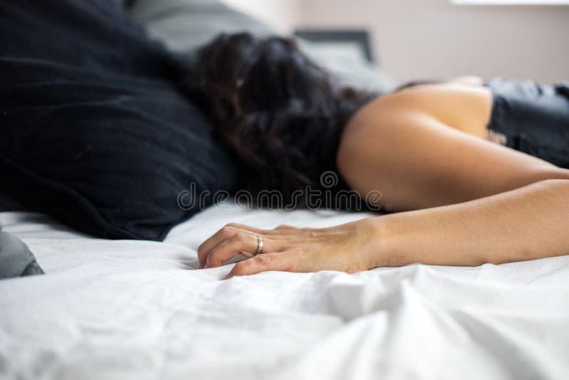 一不可能验明的有夫之妇在穿一件丝绸女睡袍,当她的手劫掠对床单时,淫荡概念的床上在 免版税库存照片