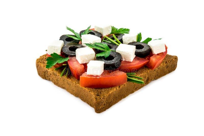 一个三明治用乳酪,橄榄,在白色的蕃茄隔绝了背景 库存照片
