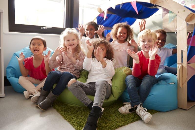 一个不同种族的小组幼儿学校孩子坐在教室,微笑的和挥动的t的一个舒适的角落的辎重袋 免版税库存照片