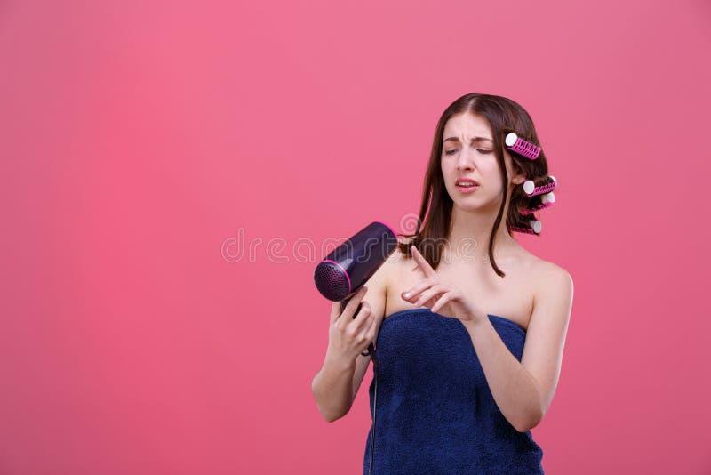一个不满意的女孩有卷发夹的和毛巾的,举行hairdryer和过于拘谨调查它 免版税库存照片