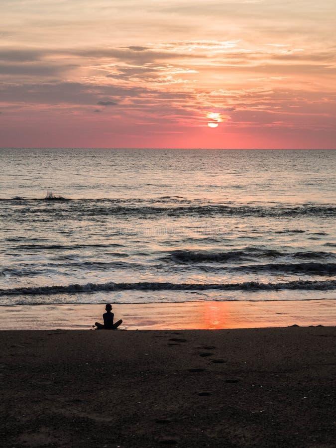 一个不确定的人的剪影莲花坐的在美好的日落期间的海沙滩 在日落期间的凝思 A 免版税图库摄影