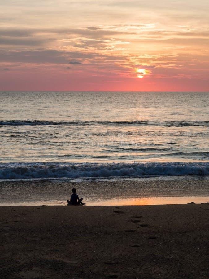 一个不确定的人的剪影莲花坐的在美好的日落期间的海沙滩 在日落期间的凝思 A 免版税库存照片