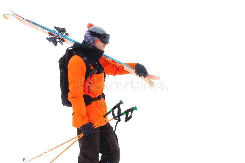 一个专业运动员滑雪者的画象戴着一个黑面具的橙色夹克的和有在他的肩膀神色的滑雪的 免版税库存图片