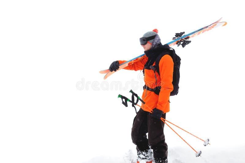 一个专业运动员滑雪者的画象戴着一个黑面具的橙色夹克的和有在他的肩膀神色的滑雪的 免版税图库摄影