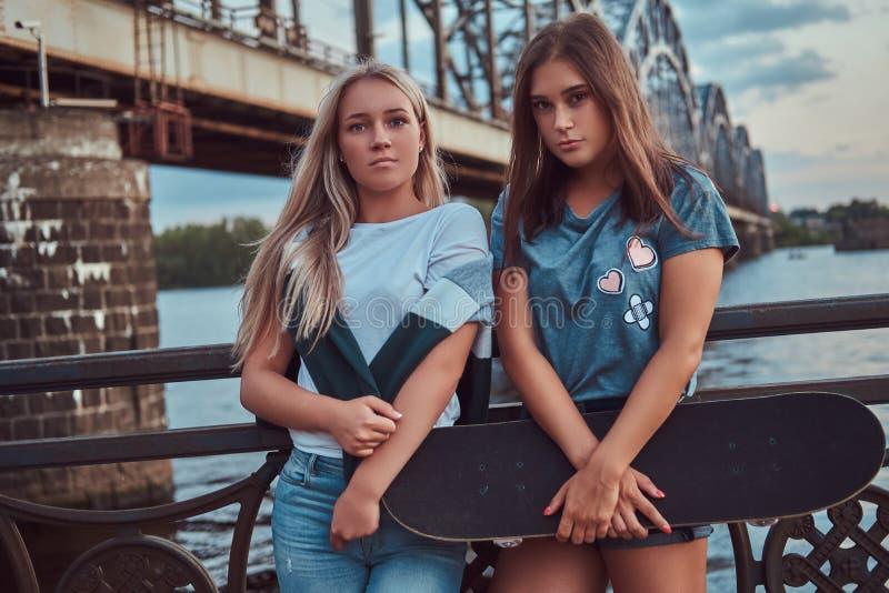 一个两个年轻人行家女孩的画象举行一个滑板和倾斜在老桥梁的背景的一根栏杆 免版税库存照片