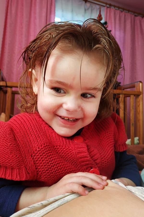 一个两岁的女孩在母亲说谎和饮料母乳、母亲团结的时期和孩子 库存图片