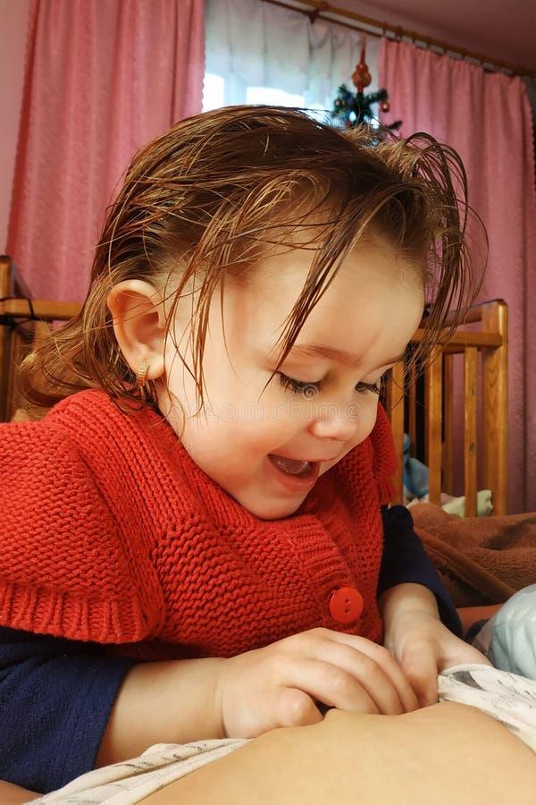 一个两岁的女孩在母亲说谎和饮料母乳、母亲团结的时期和孩子 免版税库存照片