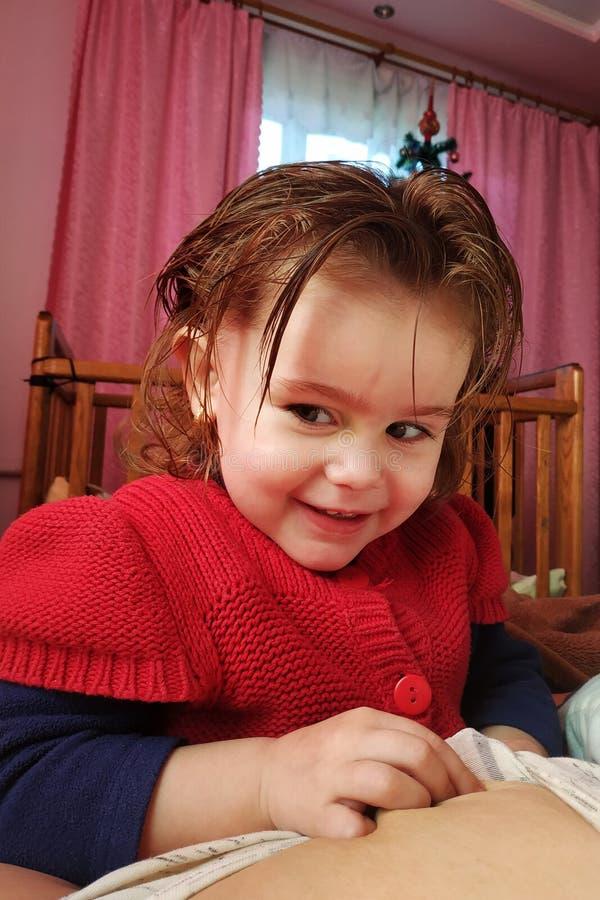 一个两岁的女孩在母亲说谎和饮料母乳、母亲团结的时期和孩子 库存照片