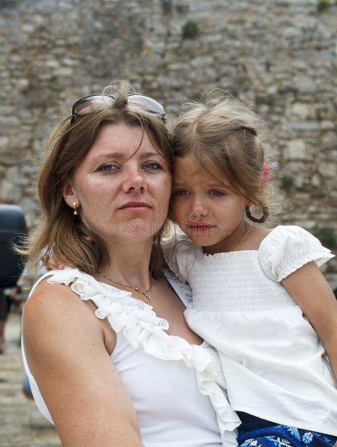 一个严肃和严密的母亲拿着调查t的一个震惊的女孩 图库摄影