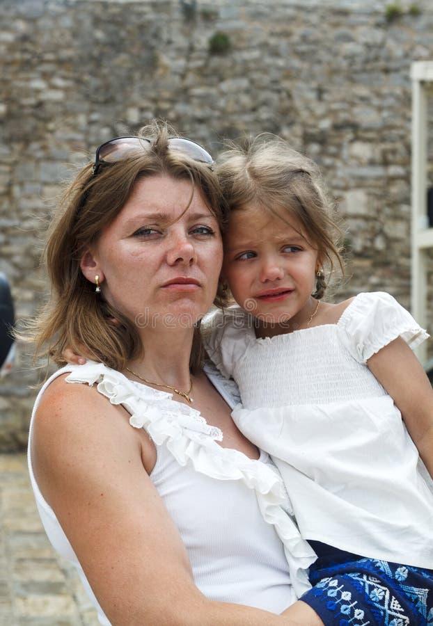 一个严肃和严密的母亲拿着调查t的一个震惊的女孩 免版税库存照片