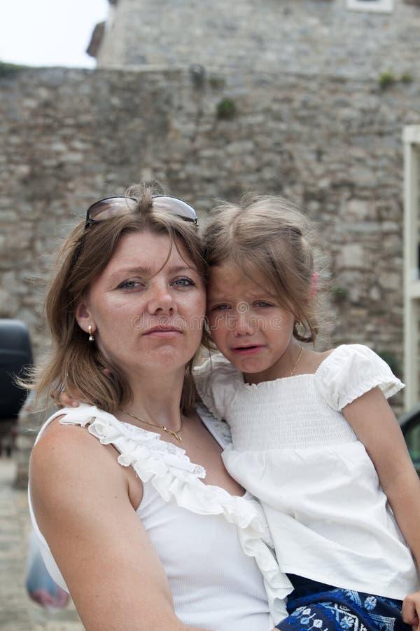 一个严肃和严密的母亲拿着调查t的一个震惊的女孩 免版税库存图片