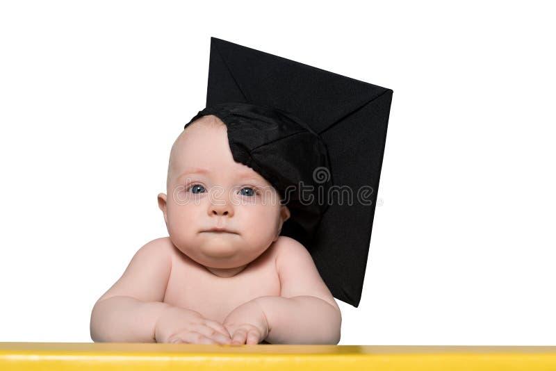 一个严肃的婴孩的画象一个学术帽子的在桌上 教育概念 ?? 免版税库存图片