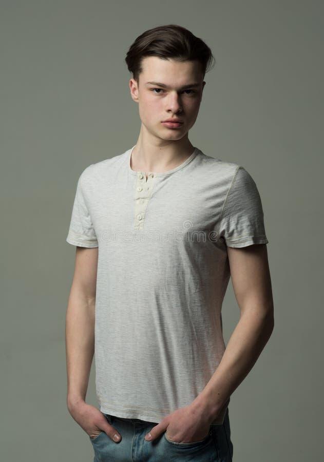 一个严肃的深色的年轻人的演播室画象有在灰色背景隔绝的中等长度头发的 英俊少年 图库摄影