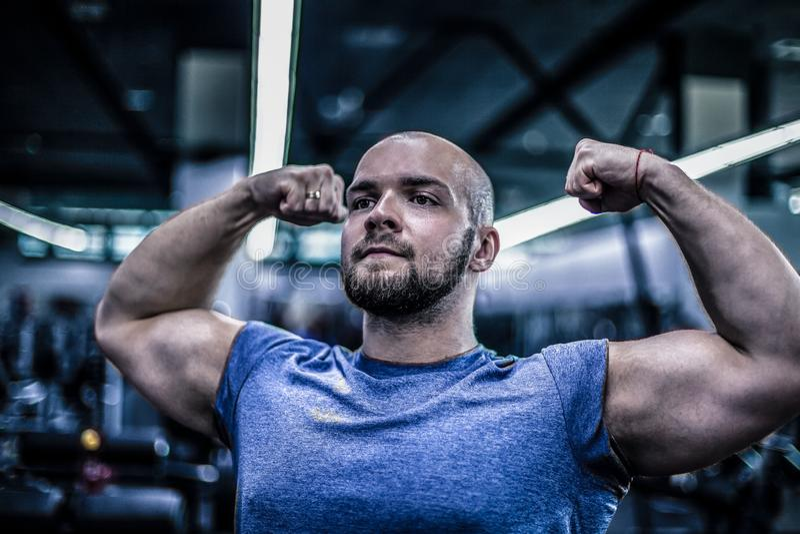 一个严肃的爱好健美者的画象有一个秃头的 展示您的二头肌 锻炼是成功的 库存照片