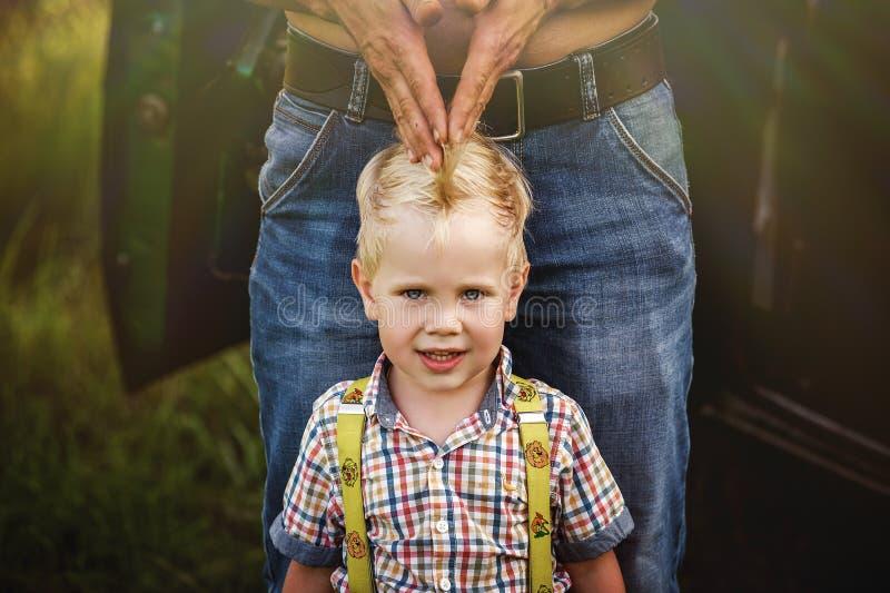 一个严肃的男婴的画象在父亲附近的在夏天 库存照片