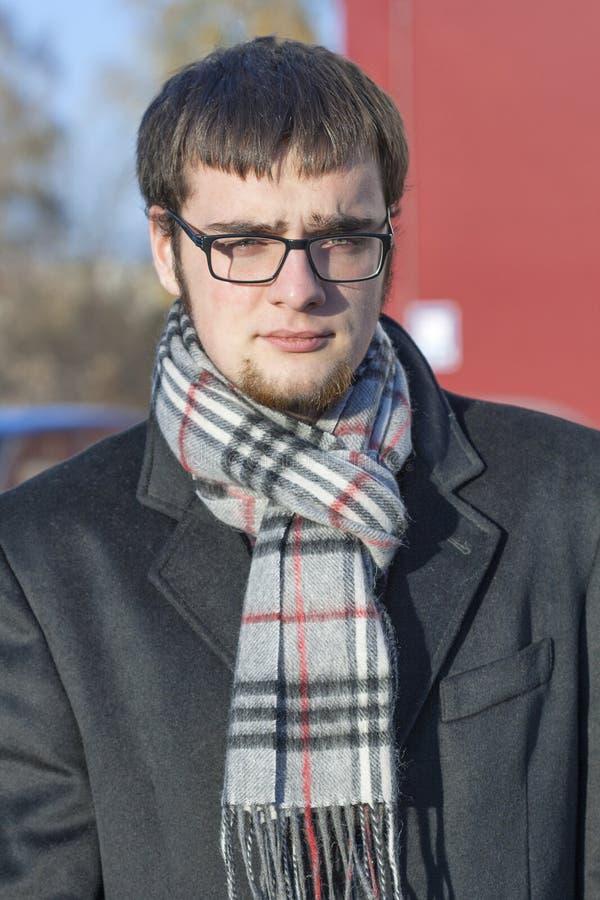 一个严肃的年轻人的画象秋天衣物的 库存图片