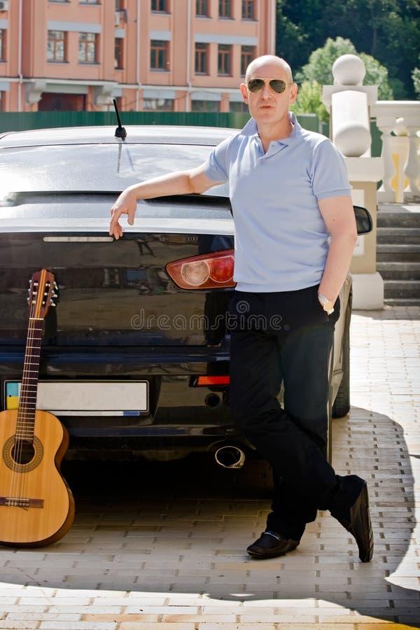 一个中年人在他的黑汽车附近站立 免版税库存图片