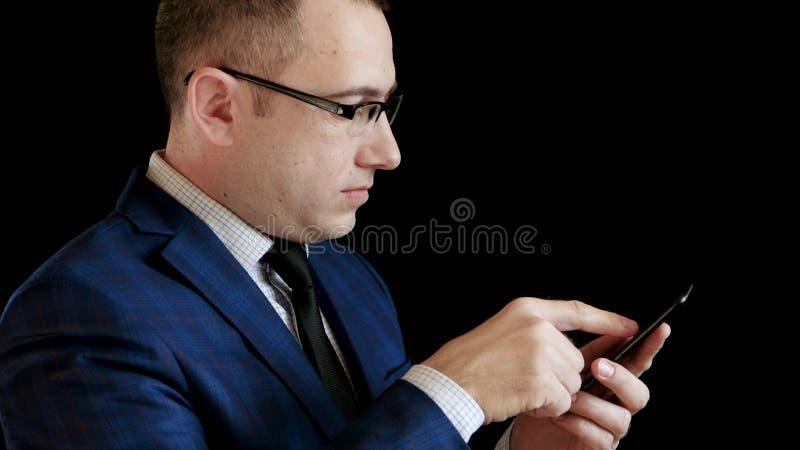 一个中年人的档案一套衣服的在黑背景 商人在互联网上工作通过他的智能手机 免版税图库摄影
