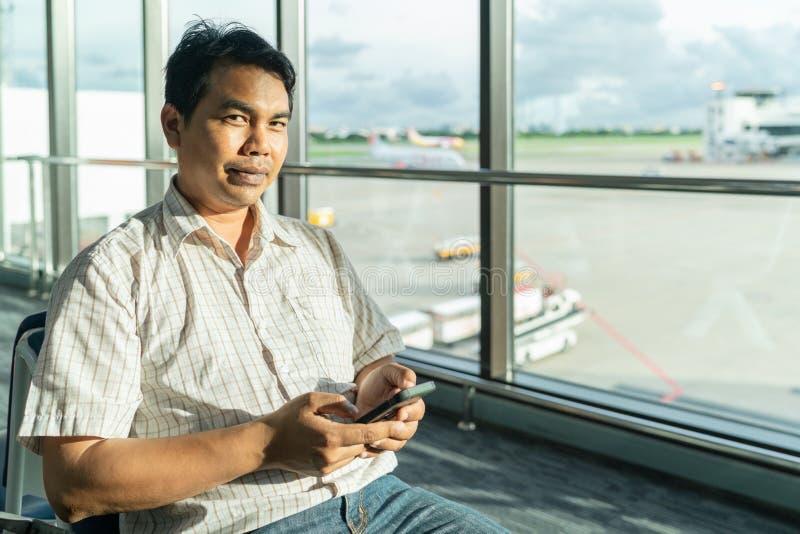 一个中年人的画象坐长凳在一玻璃窗跑道视图和用途智能手机,与看看的微笑附近在的照相机 免版税库存照片