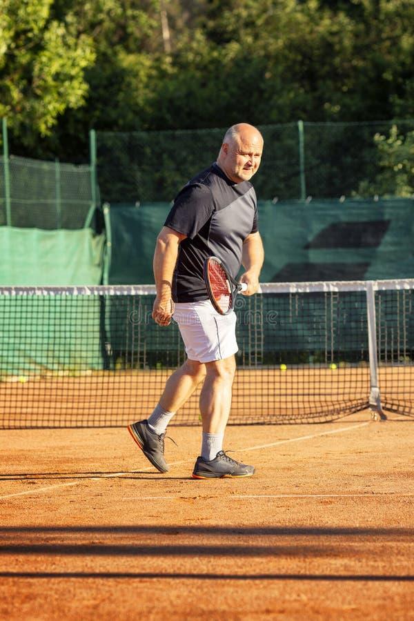 一个中年秃头人情感地打在法院的网球 失去对手 ?? 库存照片