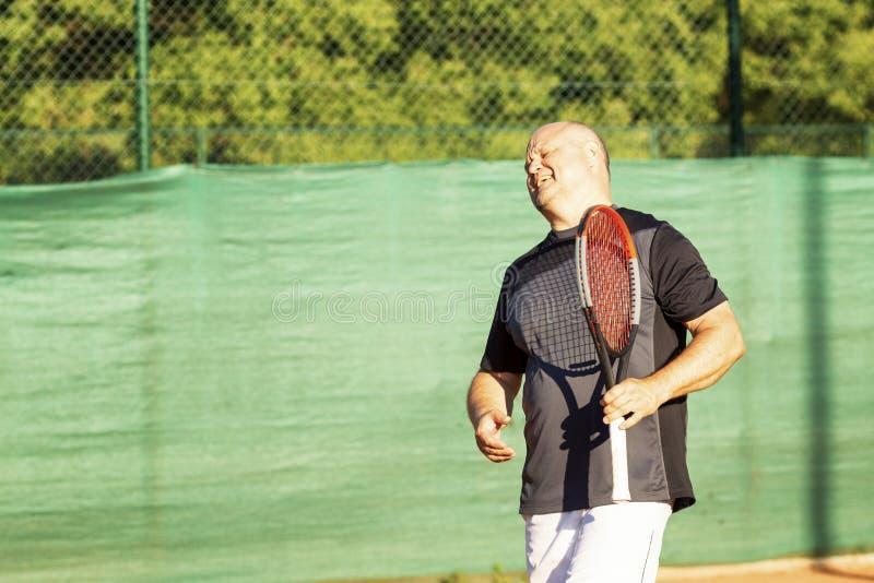 一个中年秃头人情感地打在法院的网球 失去对手 ?? 免版税库存照片