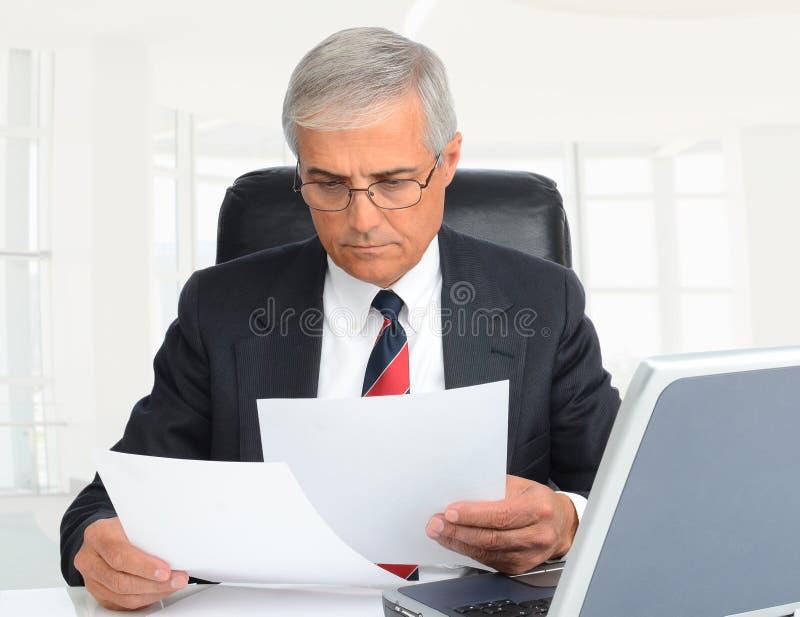 一个中间年迈的商人的特写镜头坐在这张的书桌看起来在一个现代高关键办公室设置的文件 库存图片