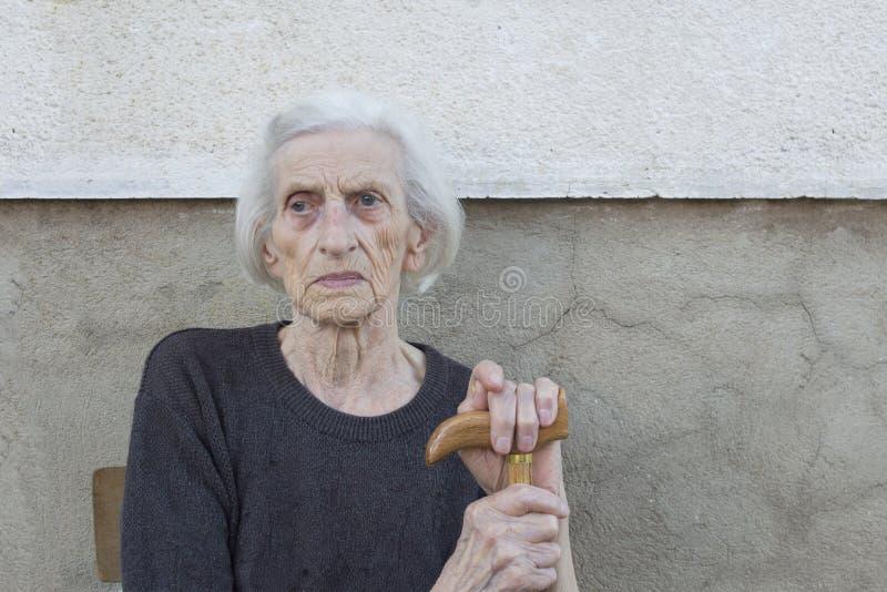 一个九十个岁祖母的画象有拐棍outdoo的 免版税库存图片